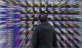 El Ibex-35 cerró el viernes con el descenso semanal más acusado desde finales de septiembre y retornó a niveles mínimos no vistos desde finales del pasado año, arrastrado por el levantamiento la víspera del veto de posiciones cortas e indicadores exteriores que se sumaron al sentimiento negativo. En la imagen, un hombre mira una pantalla con índices bursátiles en Tokio, el 30 de enero de 2013. REUTERS/Toru Hanai