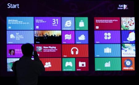 A man takes pictures of a monitor during an event promoting the debut of Microsoft Corp's Windows 8 operating system at the Akihabara electronic shops district in Tokyo October 25, 2012. REUTERS/Toru Hanai/Files