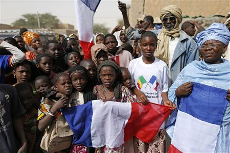 Children celebrate holding a French flag during the reopening ceremony of Mahamane Fondogoumo elementary school in the town centre of Timbuktu February 1, 2013. REUTERS/Benoit Tessier