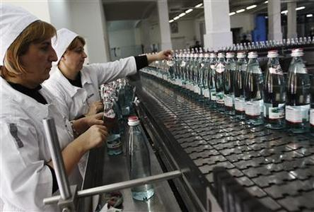 Employees work at the production line of the IDS Borjomi Georgia's factory in the town of Borjomi, some 150 km (93 miles) southwest of Tbilisi, January 30, 2013. If there's a secret to taking the bitter taste out of ties between Russia and Georgia after a 2008 war, it may lie in this lush valley south of the Caucasus Mountain border between the feuding former Soviet republics. The valley is the source of Borjomi, a salty, sulphurous mineral water that was popular in Russia since Soviet times but was swept off shelves when Moscow banned imports of Georgian beverages in 2006, with tensions already building toward war. Picture taken January 30. To match story GEORGIA-RUSSIA/TALKS REUTERS/David Mdzinarishvili