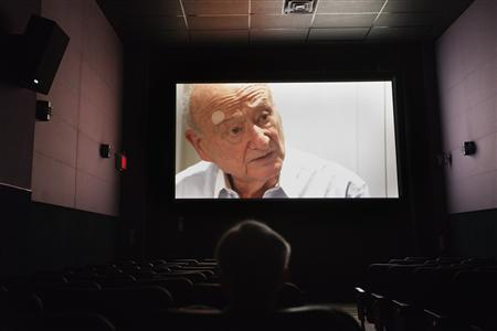 A man watches the documentary film ''Koch'', about former New York City mayor Ed Koch, at the Angelika Film Center in New York, February 1, 2013. Koch, the voluble three-term mayor who helped bring New York back from the brink of fiscal ruin in the 1970s and came to embody the city with his wry, outspoken style, died on Friday at the age of 88. REUTERS/Lucas Jackson