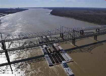 A tug pushing 35 barges passes under the Vicksburg, Mississippi bridges before making its way past oil removal operations on the Mississippi River in this U.S. Coast Guard handout photo taken January 31, 2013. More than 60 vessels and 900 barges have been cleared through the safety zone between mile marker 425 and mile marker 441, according the Coast Guard. REUTERS/Petty Officer 3rd Class Jonathan Lally/U.S. Coast Guard/Handout
