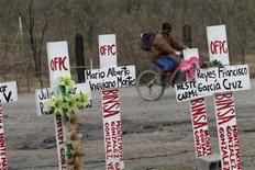 A cyclist rides past crosses set up for deceased miners in Sabinas January 15, 2013. Everyday, thousands of miners go to work in the unregulated coals mines of northern Mexico knowing they may not return. Facing death on a daily basis has become a fact of life for these men as they struggle to scrape out a living in an environment bereft of rules and regulations, lacking even the most basic equipment. Unregulated mines are legal in Mexico. A company buys or leases land from a cooperative and is legally allowed to mine on it, but is not subject to any regulations. Despite the dangers, some 30,000 miners find themselves willing to take the risk, approaching their job with a matter-of-fact philosophy. Picture taken January 15, 2013. REUTERS/Daniel Becerril