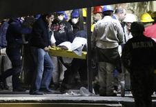 Trabalhadores carregam corpo de local da explosão na sede da petrolífera estatal mexicana Pemex, na Cidade do México. 01/02/2013 REUTERS/Bernardo Montoya