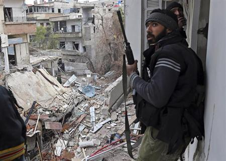 A Free Syrian Army fighter walks in a building destroyed during clashes in the Haresta neighbourhood of Damascus February 1, 2013. REUTERS/Goran Tomasevic