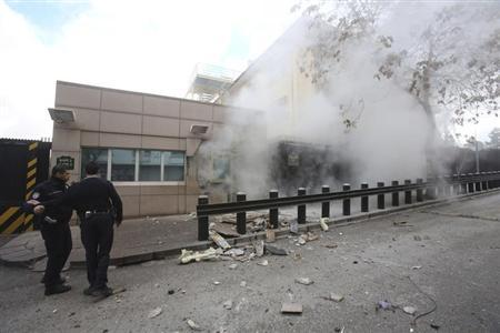 Turkish police officers react after an explosion at the entrance of the U.S. Embassy in Ankara February 1, 2013 in this picture provided by Milliyet Daily Newspaper. REUTERS/Yavuz Ozden/Milliyet Daily Newspaper/Handout