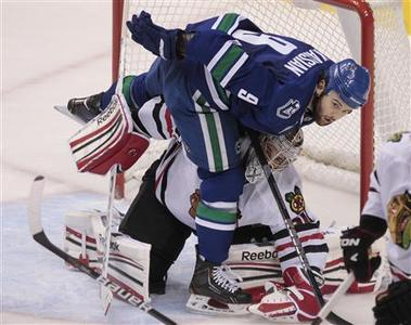 Vancouver Canucks' Zack Kassian steps over Chicago Blackhawks' goaltender Corey Crawford during the second period of their NHL hockey game in Vancouver, British Columbia February 1, 2013. REUTERS/Ben Nelms