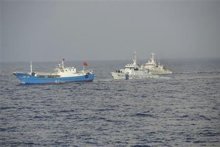 A Chinese fishing boat (L) is pursued by a Japan Coast Guard vessels in waters east-northeast of Miyako Island, Okinawa prefecture, in this handout released by 11th Regional Coast Guard Headquarters-Japan Coast Guard February 2, 2013. REUTERS/11th Regional Coast Guard Headquarters-Japan Coast Guard/Handout