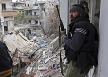 A Free Syrian Army fighter walks in a building destroyed during clashes in the Haresta neighbourhood of Damascus February 1, 2013. REUTERS/Goran Tomasevic (SYRIA - Tags: CIVIL UNREST POLITICS)