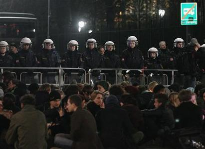 Protesters sit in front of police barriers during a demonstration against an Austrian Freedom Party (FPOe) ball in Vienna February 1, 2013. REUTERS/Heinz-Peter Bader