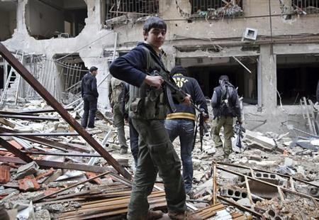 A Free Syrian Army fighter walks in front of a building destroyed during clashes in the Haresta neighbourhood of Damascus February 1, 2013. REUTERS/Mohammed Abdullah (SYRIA - Tags: CIVIL UNREST POLITICS)