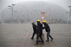 Pekín pidió el viernes a sus habitantes que lanzaran una cantidad menor de fuegos artificiales durante el período del Año Nuevo chino que se celebra este mes debido a la notoria niebla de la capital china, ya que se enfrenta a una crisis persistente en cuanto a calidad del aire. En la imagen, de 31 de enero, varios trabajadores llevan cajas en el parque olímpico de Pekín en un día de niebla. REUTERS/China Daily