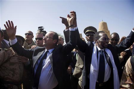 France's President Francois Hollande (L) and Mali's interim president Dioncounda Traore (R), wave upon his arrival at the airport of Timbuktu during his one-day visit in Mali February 2, 2013. French President Hollande flew to Mali on Saturday to support French troops fighting Islamist rebels in the Sahel nation and he visited the famed ancient city of Timbuktu that was recaptured from al Qaeda-allied fighters six days ago. REUTERS/Fred Dufour/Pool