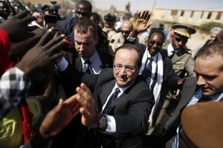 France's President Francois Hollande greets people in the center of Timbuktu February 2, 2013. Malians chanting ''Thank you, France!'' mobbed Hollande on Saturday as he visited the desert city of Timbuktu, retaken from Islamist rebels, and pledged France's sustained support for Mali to expel jihadists. REUTERS/Benoit Tessier (MALI - Tags: POLITICS CIVIL UNREST CONFLICT TPX IMAGES OF THE DAY)