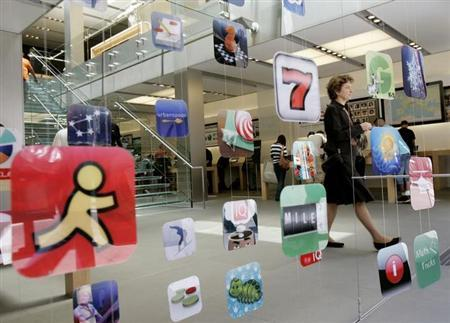 A woman walks past icons for Apple applications at the company's retail store in San Francisco, California in this April 22, 2009 file photo. REUTERS/Robert Galbraith/Files