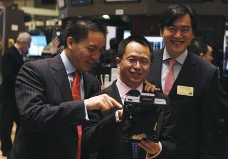 Hongyi Zhou (C), Chairman and Ceo of Qihoo 360 Technology Co Ltd takes a look at a trader's handheld trading device on the floor of the New York Stock Exchange before the company's Initial Public Offering (IPO) in New York March 30, 2011. REUTERS/Lucas Jackson/Files