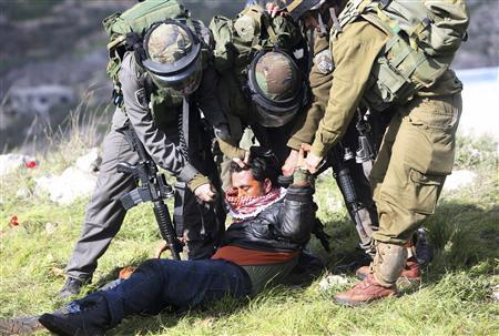 Israeli border police detain a Palestinian man after a group of activists set up tents and makeshift structures in protest against a nearby Jewish settlement in the West Bank village of Burin, south of Nablus February 2, 2013. Palestinians who set up a makeshift encampment in the occupied West Bank on Saturday clashed with Israeli soldiers and settlers and some light injuries were sustained. REUTERS/Mohamad Torokman