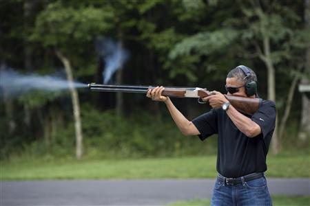 President Barack Obama shoots clay targets on the range at Camp David, Maryland, in this White House handout photo taken August 4, 2012. REUTERS/White House/Pete Souza/Handout