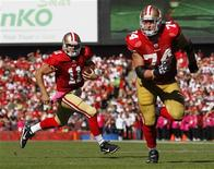 San Francisco 49ers quarterback Alex Smith (11) rushes with the ball behind his tackle Joe Staley (74) during the second quarter of their NFL football game against the Cleveland Browns in San Francisco, California, October 30, 2011. REUTERS/Beck Diefenbach