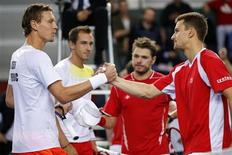 Tomas Berdych (L) of the Czech Republic and his team mate Lukas Rosol (2nd L) shake hands with Stanislas Wawrinka (2R) and Marco Chiudinelli (R) of Switzerland after winning their Davis Cup world group round 1 tennis doubles match at Palexpo in Geneva February 2, 2013. With a duration of seven hours and one minute, the match was the longest in Davis Cup history. REUTERS/Valentin Flauraud