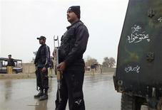 Policemen stand guard as they cordon the road leading to an isolated army checkpoint after it was attacked by militants at Lakki Marwat in the outskirts of Dera Ismail Khan February 2, 2013. REUTERS/Zahid Mohammad