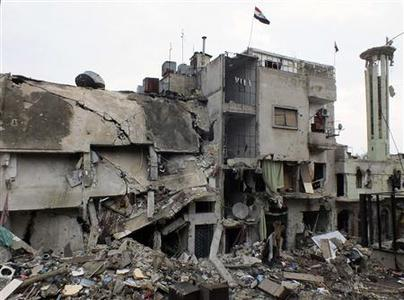 The Syrian national flag flutters atop a damaged building that was controlled by forces loyal to Syrian President Bashar al Assad in Homs January 30, 2013. REUTERS/Yazan Homsy
