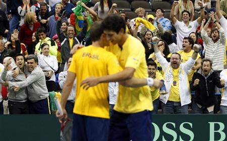 Brazil's Bruno Soares (L) and Marcelo Melo (R) embrace as fans celebrate behind them after winning their Davis Cup tennis men's double match against Bob and Mike Bryan of the U.S. in Jacksonville, Florida February 2, 2013. REUTERS/Daron Dean (UNITED STATES - Tags: SPORT TENNIS)