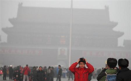 A tourist adjusts his hat for a photo in front of the giant portrait of former Chinese Chairman Mao Zedong at Tiananmen Square on a foggy day in central Beijing, January 31, 2013. REUTERS/China Daily