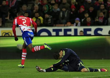 Real Madrid's Cristiano Ronaldo (R) falls next to Granada's Odion Jude Ighalo during their Spanish First Division soccer match at Los Carmenes stadium in Granada February 2, 2013. REUTERS/Marcelo del Pozo