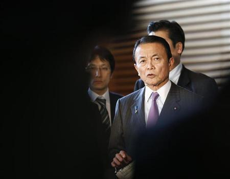 Japan's Finance Minister Taro Aso is seen in-between reporters while he speaks at a joint news conference with Bank of Japan Governor Masaaki Shirakawa and Economics Minister Akira Amari after their briefing to Prime Minister Shinzo Abe (not pictured) in Tokyo January 22, 2013. REUTERS/Kim Kyung-Hoon