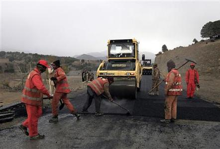 A military soldier stands near labourers working on the construction of the Wana Jandola road in Wana, in Pakistan's South Waziristan tribal region bordering Afghanistan November 28, 2012. Picture taken on November 28, 2012. REUTERS/Faisal Mahmood