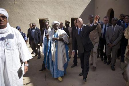France's President Francois Hollande (R) walks ahead of Mali's interim president Dioncounda Traore (3rdR, partially hidden), as they visit the Grand Mosque in Timbuktu, during his one-day visit to Mali, February 2, 2013. REUTERS/Fred Dufour/Pool