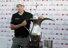 Stephen Gallacher of Scotland poses with the trophy at the 18th green after the fourth and final round of the Dubai Desert Classic at the Emirates Golf Club February 3, 2013. Gallacher won the Dubai Desert Classic on Sunday with a final-round 71 for a total of 266 in the European Tour golf event. REUTERS/Jumana El Heloueh