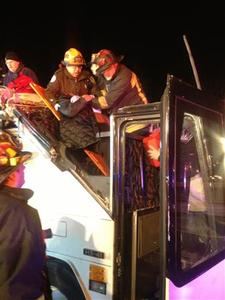 First responders assist injured passensers from a charter bus that crashed in Boston, Massachusettes February 2, 2013. The bus was carrying 42 passengers traveling from Harvard University in Cambridge, Massachusetts, to Pennsylvania when it crashed into a Boston overpass on Saturday night, injuring 33 people, according to emergency officials. REUTERS/Boston Fire Dept./Handout