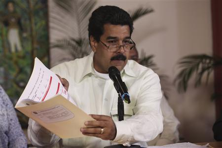 Venezuela's Vice President Nicolas Maduro shows a document which he said has the signature of ailing President Hugo Chavez as he speaks to state TV after arriving from Cuba in Caracas January 26, 2013. REUTERS/Miraflores Palace/Handout