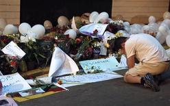 Homem ajoelha em frente a tributos em homenagem às vítimas do incêndio na boate Kioss, em Santa Maria. O número de vítimas fatais em decorrência do incêndio no Rio Grande do Sul aumentou para 237 na noite de sábado, informou a Secretaria de Saúde do Estado. 28/01/2013 REUTERS/Edison Vara