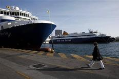 A woman walks immobilised ships which ceased operations during a strike, at a promenade of Piraeus port near Athens February 3, 2013. Greek seamen extended a strike to protest government austerity for a further 48 hours on Sunday, meaning that dozens of islands will have been cut off from the mainland for six days. REUTERS/Yorgos Karahalis