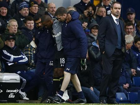 Tottenham Hotspur's Jermain Defoe is carried off with an injury as West Bromwich Albion's manager Steve Clarke (R) watches during their English Premier League soccer match at The Hawthorns in West Bromwich, central England, February 3, 2013. REUTERS/Darren Staples