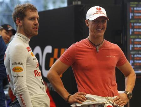 Driver Michael Schumacher (R) from Team Germany speaks with his compatriot Sebastian Vettel before a practice for the Race of Champions (ROC) at the Rajamangala National Stadium in Bangkok December 16, 2012. REUTERS/Chaiwat Subprasom/Files