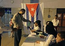 An election official gives a man ballot papers at a special polling station set up in Havana's main train station February 3, 2013. Cubans go to polls to elect National Assembly representatives. REUTERS/Desmond Boylan (CUBA - Tags: POLITICS ELECTIONS)