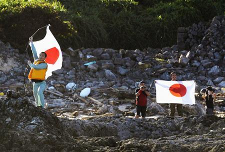 Members of a Japanese nationalist group raise Japanese flags as they land on Uotsuri island, part of the disputed islands in the East China Sea, known as the Senkaku isles in Japan and Diaoyu islands in China, in this photo by Kyodo August 19, 2012. REUTERS/Kyodo