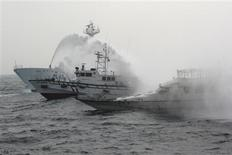 A Japan Coast Guard patrol ship (L) sprays water at a fishing boat (R) carrying Taiwanese activists onboard while it heads for the disputed East China Sea islets called the Senkaku in Japan, the Diaoyu in China and the Tiaoyutai in Taiwan, as a Taiwan Coast Guard ship (C) attempts to protect the fishing boat, in this January 24, 2013 file handout photo provided by the Taiwan Coast Guard.REUTERS/Taiwan Coast Guard/Handout/Files