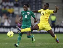 Le Burkina Faso s'est hissé en demi-finale de la Coupe d'Afrique des nations en battant le Togo 1-0 grâce à un but de Jonathan Pitroipa (à gauche), ici à la lutte avec Dakonam Djene, lors de la prolongation. /Photo prise le 3 février 2013/REUTERS/Thomas Mukoya