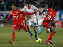 Le Marseillais André-Pierre Gignac (au centre) à la lutte avec les Nancéiens Yassine Jebbour (à gauche) et Salif Sane, au Stade Vélodrome. Les hommes d'Elie Baup se sont inclinés 0-1 devant les Lorrains, bons derniers de Ligue 1 avant le coup d'envoi. Le Paris Saint-Germain, vainqueur vendredi à Toulouse (4-0) est désormais seul en tête, avec trois longueurs d'avance sur les Lyonnais et six sur les Marseillais. /Photo prise le 3 février 2013/REUTERS/Jean-Paul Pelissier