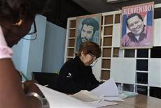 Election officials sit at a table near pictures of Latin American revolutionary Ernesto Che Guevara (L) and Venezuela's President Hugo Chavez in Havana February 3, 2013. REUTERS/Enrique De La Osa