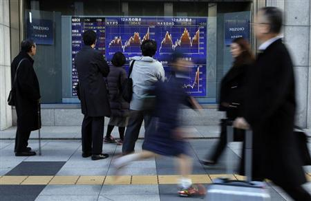 People look at a stock index board outside a brokerage in Tokyo January 30, 2013. REUTERS/Toru Hanai