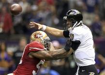 Baltimore Ravens quarterback Joe Flacco (5) passes under pressure from San Francisco 49ers inside linebacker NaVorro Bowman (53) during the fourth quarter in the NFL Super Bowl XLVII football game in New Orleans, Louisiana, February 3, 2013. REUTERS/Sean Gardner