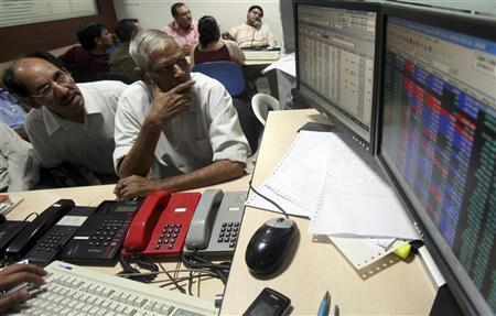 Investors watch the share index at a local share market in Chandigarh October 10, 2008. REUTERS/Ajay Verma/Files