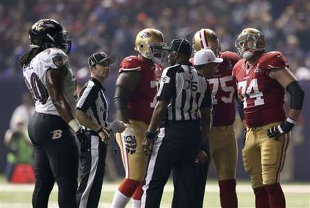San Francisco 49ers and Baltimore Ravens players gather on the field during a power outage in the NFL Super Bowl XLVII football game in New Orleans, Louisiana, February 3, 2013. REUTERS/Sean Gardner