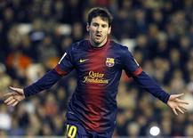 Lionel Messi marcó su decimosegundo gol consecutivo en Liga que permitió a los líderes, el Barcelona empatar 1-1 en Valencia, lo que a su vez posibilitó que su único perseguidor, el Atlético de Madrid le recortara su gran ventaja tras ganar 1-0 al Betis en el Vicente Calderón. En la imagen, de 3 de febrero, Lionel Messi celebra el gol de penalti que le encajó al Valencia en Mestalla. REUTERS/Heino Kalis
